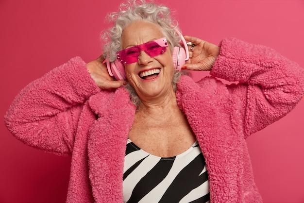 Крупным планом портрет счастливой морщинистой модной бабушки в розовых колготках и пальто
