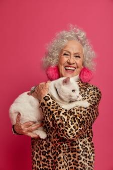 美しい猫と幸せなしわのファッショナブルなおばあちゃんの肖像画をクローズアップ