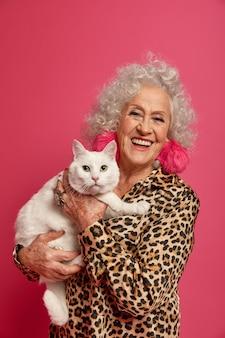 Крупным планом портрет счастливой морщинистой модной бабушки с красивой кошкой