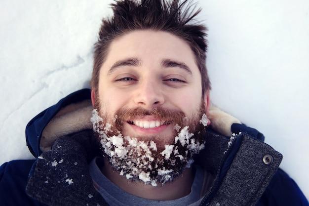 冬の寒さで幸せな若いひげを生やした男の肖像画を間近します。楽しい男笑顔。
