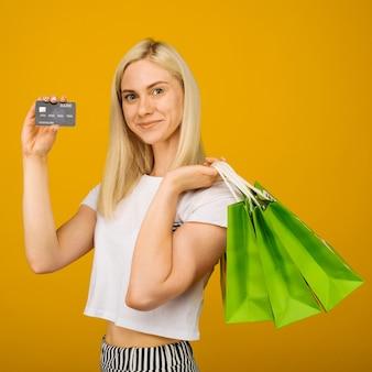 노란색에 카메라를보고 신용 카드와 녹색 쇼핑 가방을 들고 행복 젊은 아름 다운 금발 여자의 클로즈업 초상화