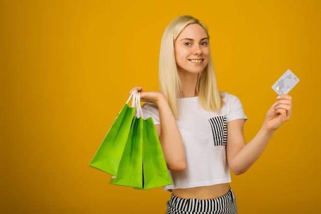 Портрет крупным планом счастливой молодой красивой блондинки, держащей кредитную карту и зеленые хозяйственные сумки