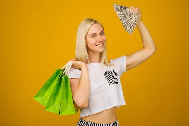 Крупным планом портрет счастливой молодой красивой блондинки, держащей деньги и зеленые хозяйственные сумки, глядя в камеру, на желтом