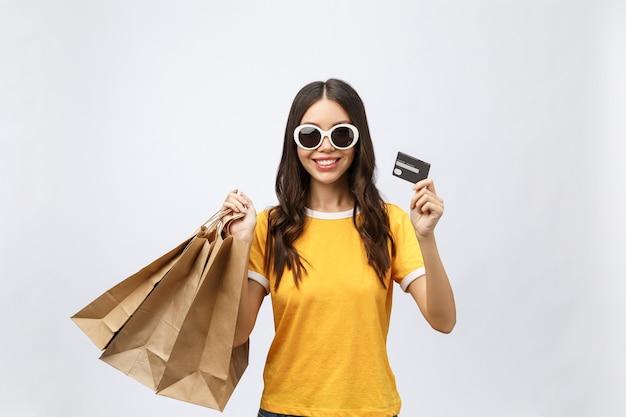 Крупным планом портрет счастливой молодой женщины брюнетки в солнцезащитных очках, держащей кредитную карту и красочные сумки для покупок
