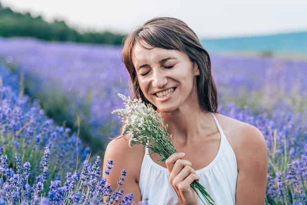 咲く香りのよいラベンダー畑に白いドレスを着て幸せな若いブルネットの女性の肖像画をクローズアップ