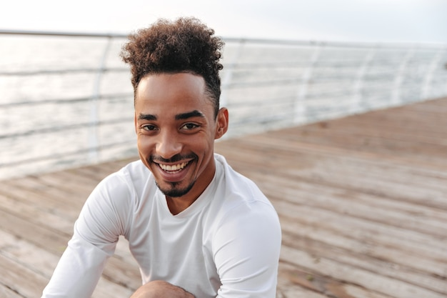 海の近くで心から笑っている白いスポーツの長袖tシャツで幸せな若い浅黒い肌の男のクローズアップの肖像画