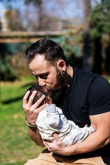 彼の甘い愛らしい新生児を抱きしめてキスする幸せな若い父親の肖像画を閉じます。