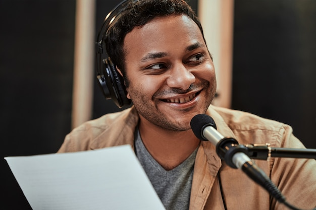 말하는 동안 옆으로 웃으면서 헤드폰을 끼고 행복한 젊은 남성 라디오 진행자의 초상화를 클로즈업