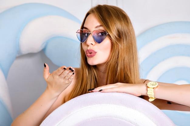巨大なキャンディー、長い髪と美しさの笑顔の近くのスタジオでポーズをとって、心のこもったサングラスと時計、ポップスタイルを身に着けている幸せな若い女性の肖像画を閉じます。