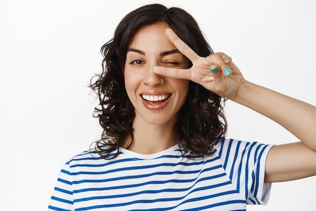 幸せな若い女性の肖像画をクローズアップ、まばたきと平和のvサインジェスチャー、カワイイサイン、白い歯の笑顔、白の上に陽気に立っている