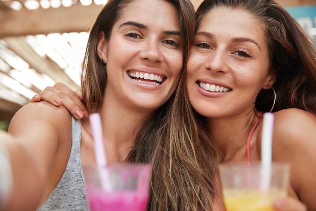 행복 한 젊은 여성의 초상화를 닫고 행복하게 미소 짓고 흰색 완벽한 치아를 가지고 셀카를 만들고 신선한 칵테일을 마실 수 있습니다.