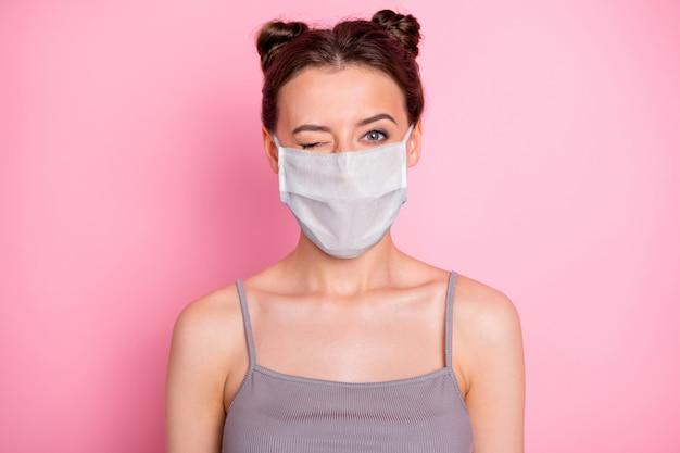 Портрет крупным планом ее привлекательной девушки, подмигивающей в многоразовой маске, профилактика респираторных заболеваний, вакцина против синдрома гриппа нового типа, изолированная на розовом фоне пастельных тонов