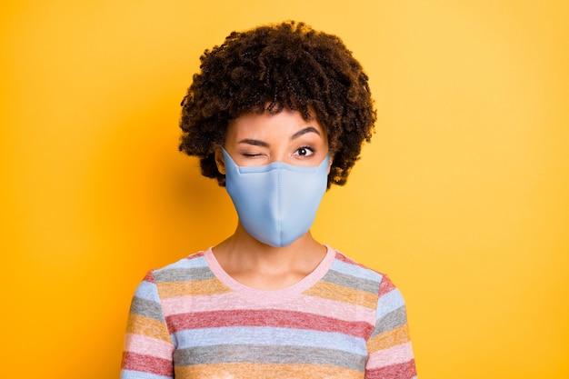 Крупным планом портрет ее здоровой привлекательной фанки с волнистыми волосами в защитной многоразовой маске, подмигивающей остановить вирусное респираторное заболевание, изолированное яркое яркое сияние, яркий желтый цвет фона