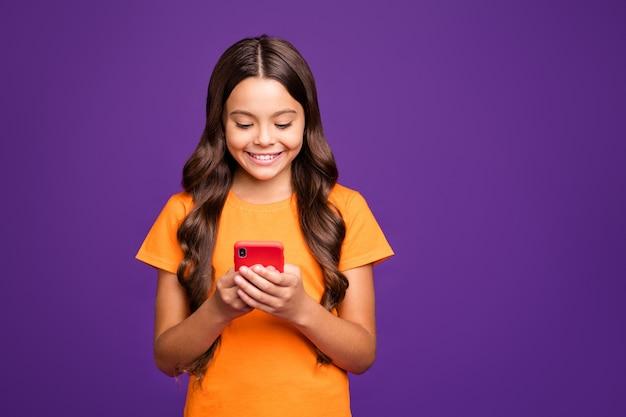 彼女のクローズアップの肖像画彼女の素敵な魅力的な魅力的な素敵な陽気な陽気なウェーブのかかった髪の少女は、明るい鮮やかな輝きの鮮やかなライラック紫紫の色の背景に分離されたデジタルガジェット5gアプリを使用しています