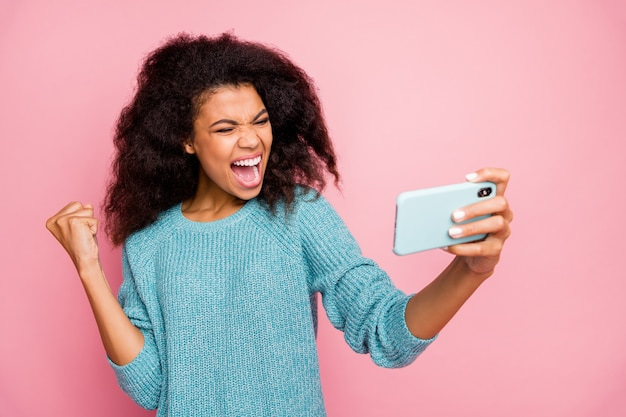 Крупным планом портрет ее красивой привлекательной веселой веселой счастливой волнистой девушки, использующей гаджет для цифрового устройства, весело проводящей время, изолированной на стене в пастельных тонах