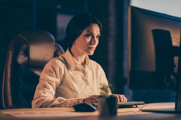 Портрет крупным планом, она красивая, привлекательная, великолепная, прекрасная, очаровательная, сосредоточенная, занятая, копирайтер, печатает, создавая анализ отчета о презентации, ночью, в темноте, на рабочем месте, в помещении.