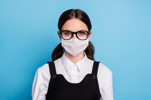 彼女のクローズアップの肖像画安全マスクを身に着けている彼女の素敵な魅力的なインテリジェント勤勉な健康な女の子は汚染を停止しますmerscovインフルエンザ病予防孤立した青い色の背景