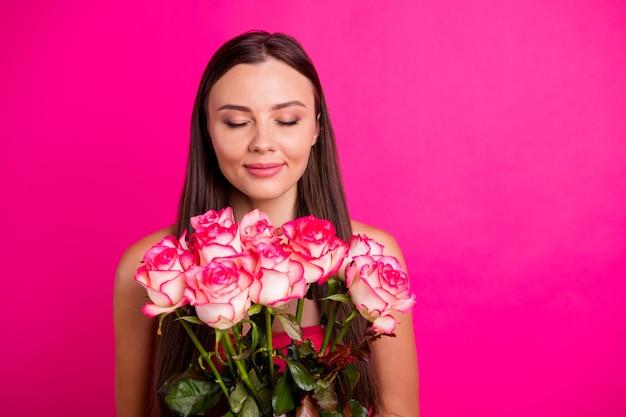 彼女のクローズアップの肖像画彼女の素敵な魅力的な素敵な穏やかな平和で陽気な長髪の少女が手に持って明るい鮮やかな輝きの鮮やかなピンクのフクシア色の背景に分離された花束の香りを嗅ぐ