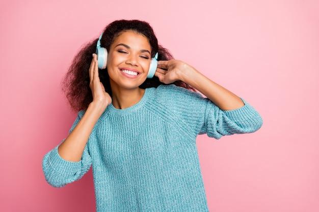 Портрет крупным планом она милая привлекательная милая очаровательная веселая мечтательная девушка с волнистыми волосами слушает рок-джаз-фанк мелодию аудио стерео, изолированную над розовой пастельной стеной