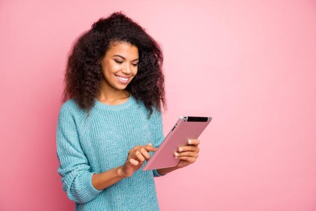 ピンクのパステルカラーの壁に分離されたwi-fiスマートガジェット読書ニュースを使用して彼女の素敵な魅力的な素敵な魅力的なかわいい陽気な陽気なウェーブのかかった髪の少女のクローズアップの肖像画
