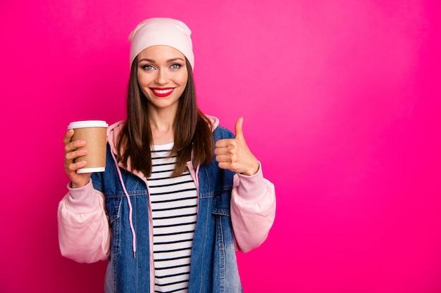 彼女の素敵な魅力的な素敵な陽気な陽気な女の子のクローズアップの肖像画は、明るい鮮やかな輝きの鮮やかなピンクのフクシア色の上に分離されたサムアップを示すお茶の紙コップを手に持っています