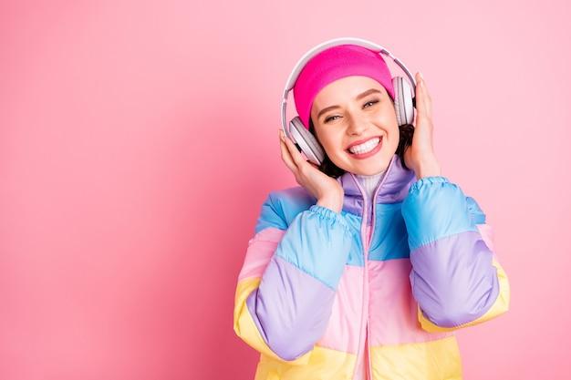 Портрет крупным планом, она милая, привлекательная, милая, веселая, веселая, радостная, девушка, наслаждающаяся новым романтическим треком в формате mp3, изолирована на розовом пастельном фоне
