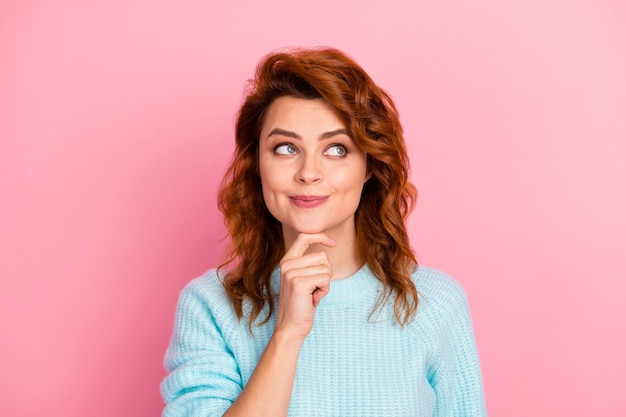 彼女の素敵な魅力的な素敵なかわいいかわいいかなり魅力的な創造的な陽気なウェーブのかかった髪の少女のクローズアップの肖像画は、ピンクのパステルカラーの背景の上に分離された新しいソリューションの決定を作成します