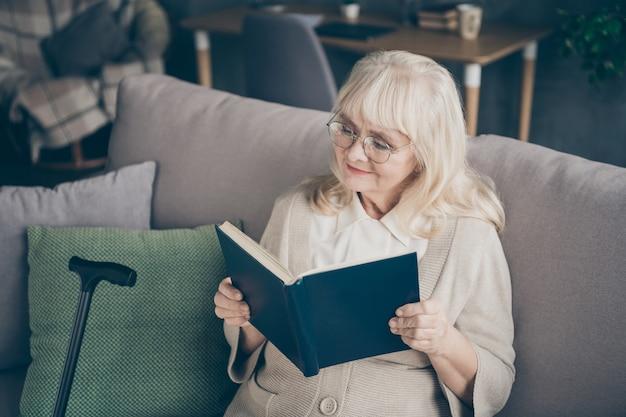彼女の素敵な魅力的な素敵な焦点を当てた白髪の女性のクローズアップの肖像画は、屋内のフラットハウスのアパートで引退を過ごす興味深い小説を読んでいます