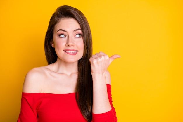 그녀의 클로즈 업 초상화는 그녀의 멋지고 매력적인 사랑스럽고 호기심 많은 갈색 머리 소녀가 카피스페이스를 물고 있는 입술 모양 아이디어 광고를 보여주고 있습니다.