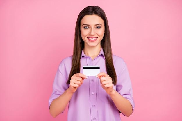 Макро портрет ее она милая привлекательная милая довольно очаровательная уверенная в себе жизнерадостная длинноволосая девушка держит в руках, демонстрируя банковскую карту, изолированную на розовом пастельном цветном фоне