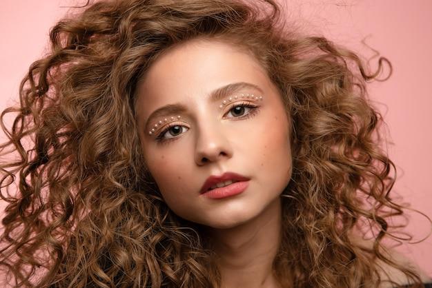 彼女のクローズアップの肖像画彼女は素敵な魅力的な素敵なかなり陽気な陽気な嬉しいウェーブのかかった髪の女の子