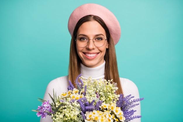 彼女のクローズアップの肖像画彼女の素敵な魅力的な素敵なかなり陽気な陽気なストレートヘアの女の子が手に持っている明るい鮮やかな輝き鮮やかな青い色の背景の上に分離された野生の花