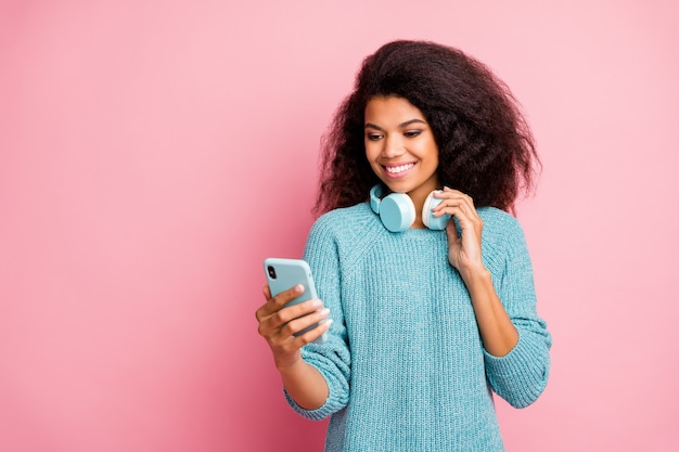 Ее портрет крупным планом она милая привлекательная милая милая очаровательная веселая веселая с волнистыми волосами девушка выбирает трек-лист хит-трек фанк джаз-рок изолирована над розовой пастельной стеной