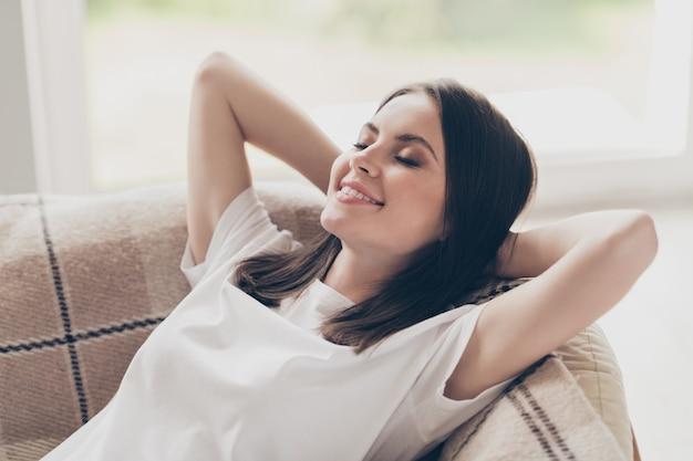 彼女の素敵な魅力的なかなり夢のような陽気な茶色の髪の少女のクローズアップの肖像画は、屋内の明るい家で休んでおはようの目覚めを楽しんでいるベッドのソファに横たわっています