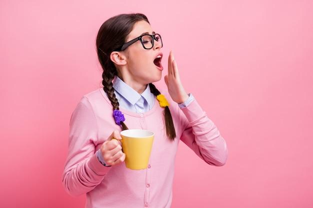 ピンクのパステルカラーの背景に分離されたカフェインあくびの目覚めを飲む彼女の素敵な魅力的なかなり知的疲れた眠そうな茶色の髪の10代の少女のクローズアップの肖像画