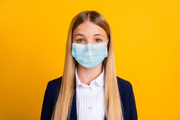 Портрет крупным планом, она симпатичная, привлекательная, довольно длинноволосая, здоровая школьница, носящая марлевую маску, остановить вирусную пневмонию, изолирована, яркий яркий блеск, яркий желтый цвет фона