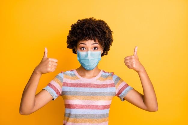 Крупным планом портрет ее красивой здоровой волнистой девушки в защитной маске, показывающей профилактику болезни большого пальца руки, изолированный яркий яркий блеск, яркий желтый цвет фона