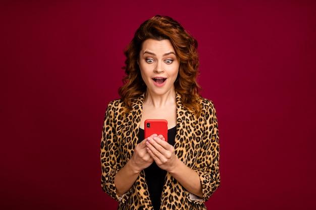 Крупным планом портрет ее красивой привлекательной очаровательной веселой изумленной волнистой девушки, использующей высокоскоростное соединение 5g сотовой связи, изолированное на красном бордовом бордовом цветном фоне марсала