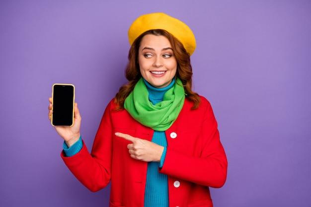 Портрет крупным планом, она симпатичная привлекательная милая рыжая веселая любопытная девушка с волнистыми волосами, показывающая рекламные советы сотовой рекламы, изолированные на фиолетово-сиреневом пурпурном пастельном цветном фоне