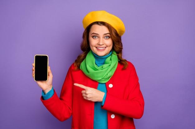 Портрет крупным планом, она красивая привлекательная милая рыжая веселая девушка с волнистыми волосами показывает рекламу нового цифрового устройства, изолированную на фиолетово-сиреневом пурпурном пастельном цвете