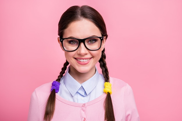 ピンクのパステルカラーの背景に分離された彼女の見栄えの良い魅力的な素敵なかわいい陽気な陽気な茶色の髪の十代の少女オタク高等教育のクローズアップの肖像画