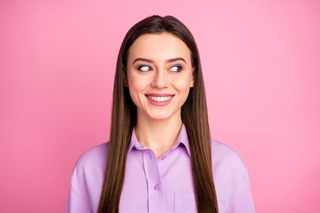 彼女のクローズアップの肖像画彼女の見栄えの良い魅力的な素敵なかわいい陽気な黒髪のストレートヘアの女の子は、ピンクのパステルカラーの背景の上に分離されたアイデアプランを推測して脇を探しています