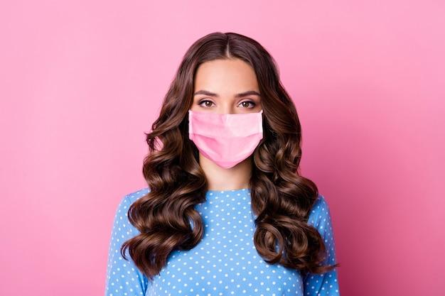 Крупным планом портрет ее красивой привлекательной красивой загорелой волнистой дамы в защитной маске, изолированной на розовом фоне пастельных тонов
