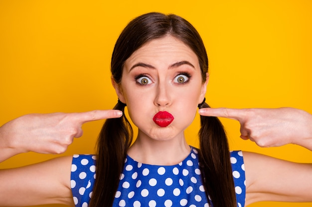 Портрет крупным планом, она красивая привлекательная довольно милая фанк-юмористическая девушка, морщась, держа воздух в щеках, указывая указательными пальцами, изолированными на ярком ярком сиянии яркого желтого цвета фона