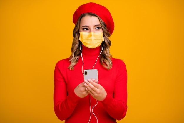 彼女のクローズアップの肖像画彼女の見栄えの良い魅力的なかわいいウェーブのかかった髪の少女が手に持っているセルリスニングロックソウルポップ音楽黄色の背景に分離された医療マスクを着用してください