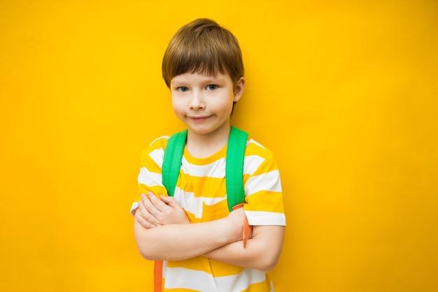 Крупный план его красивого внушительного классного любопытного жизнерадостного мальчика предподросткового возраста, изолированного ярким ярким блеском на ярком желтом фоне