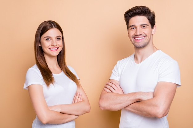 그의 클로즈 업 초상화 그는 그녀는 베이지 색 파스텔 컬러 배경 위에 절연 흰색 티셔츠 접힌 팔을 입고 그녀는 좋은 매력적인 쾌활한 쾌활한 콘텐츠 몇 동료 팀
