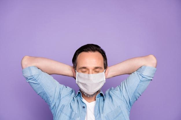 Портрет крупным планом его зрелого мечтательного парня, отдыхающего, спящего, пандемии гриппа, профилактики инфекций, самоизоляции в марлевой маске, изолированной на фиолетовом лиловом фоне фиолетового цвета