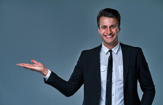 Макро портрет его он красивый привлекательный веселый веселый бизнесмен агент-брокер в черном костюме, держащий невидимый объект на пальмовом решении по рекламе, изолированном на сером фоне.
