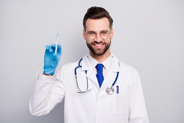 Его портрет крупным планом, он красивый, привлекательный, жизнерадостный, жизнерадостный, опытный, уверенный в себе, квалифицированный бородатый врач, фельдшер, готовит укол-вакцину, изолированный на светло-белом сером пастельном цвете